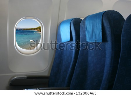 Airplane seat and window inside an aircraft with view on sea. - stock photo