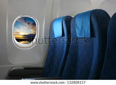 Airplane seat and window inside an aircraft with view on sea at sunset with clouds. - stock photo
