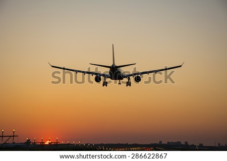 Airplane started landing during sunrise. - stock photo