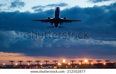 Airplane take of at dusk - stock photo