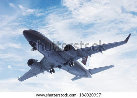 Airplane taking off. A big passenger or cargo aircraft, airline flying. Transportation, transport, business in motion. - stock photo