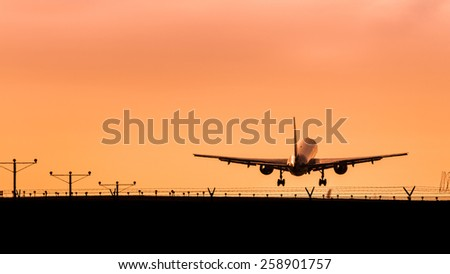 Airplane Taking Off at Sunset - stock photo