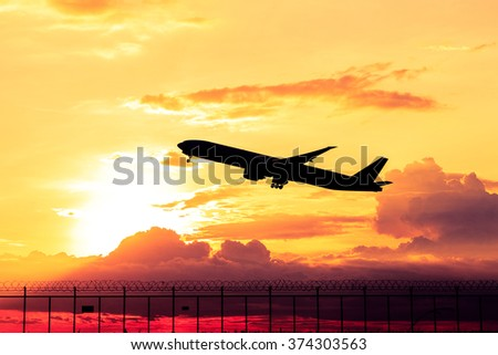 Airplane taking off at sunset. Silhouette of a big passenger or cargo aircraft, airline. Transportation - stock photo