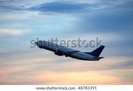 Airplane taking off into red, blue sky. - stock photo