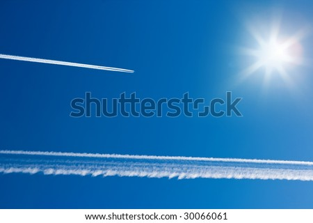 Airplane tracks and sun in the blue sky - stock photo
