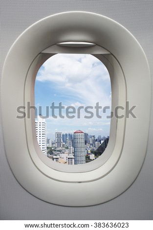 Airplane window from interior of aircraft with view of city. - stock photo