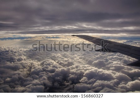 Airplane wing above the clouds from airplane window - stock photo
