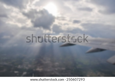 Airplane wing above the clouds Unfocused - stock photo