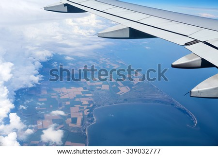 Airplane wing out of window above the clouds. Below is the land and sea blue water - stock photo