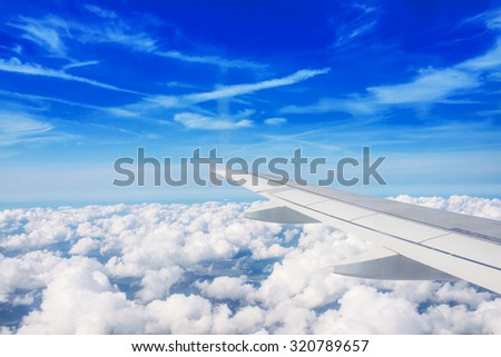 Airplane wing out of window and clouds - stock photo