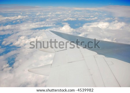 airplane wing over clouds - stock photo