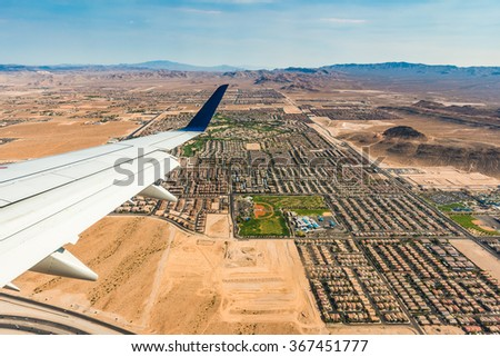 airplane wing over the desert city on sunny day. - stock photo