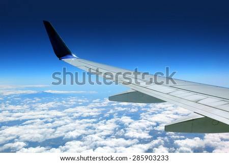 Airplane wing with blue sky  - stock photo