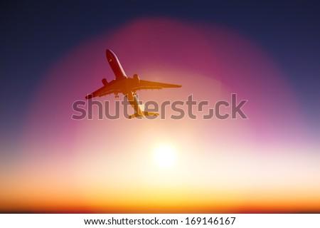 airplane with beautiful orange sunset background - stock photo