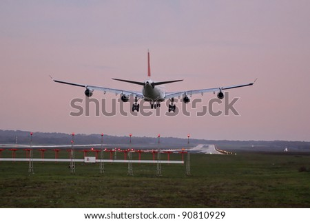 Airplane with four engines landing on runway back view - stock photo