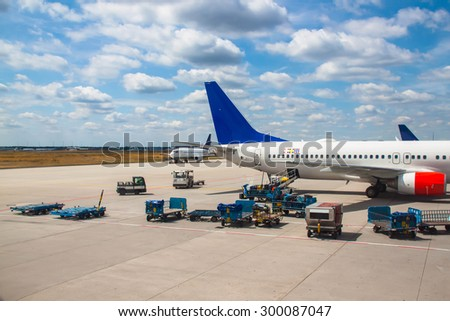 Airplanes and luggage cars on an airport - stock photo