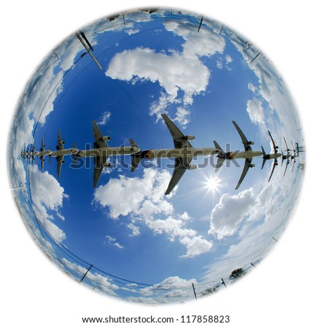 Airplanes in an earth globe with multiple airplanes and bright sunshine. - stock photo