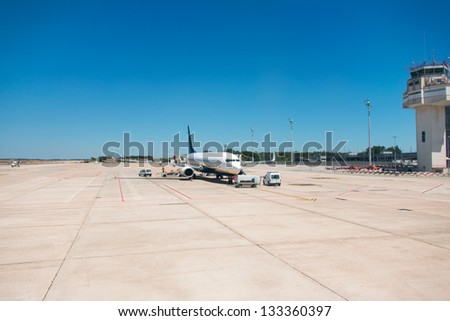 Airport. Airplane is being serviced by the ground crew. - stock photo