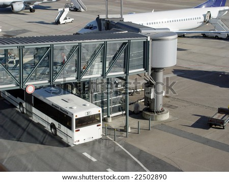 Airport bus next to gangway and airplane - stock photo