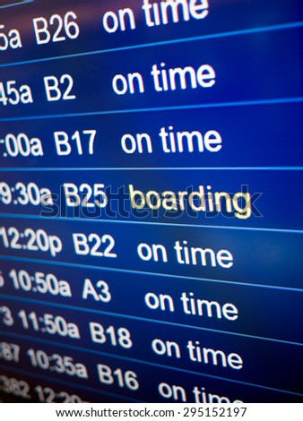 Airport flight status board. Arrival and departure board sign showing on-time and boarding status. - stock photo