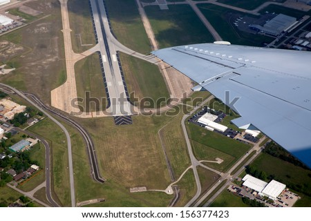 Airport landing road view from aerial view and aircraft wing - stock photo