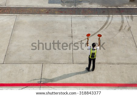 Airport marshalling signal from marshaller for aircraft controls.  Ground Crew Signals  Airport Ground Crew Outfit and Signals  A ground crew  signals the pilot - stock photo