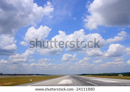 Airport runway road view under cloudy blue sky. - stock photo