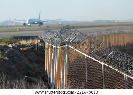 airport security mesh and barbed wire perimeter fence, with airliner. - stock photo