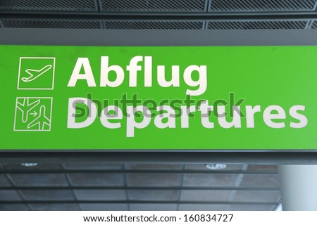 Airport sign in Germany - departures green sign in German and English - stock photo