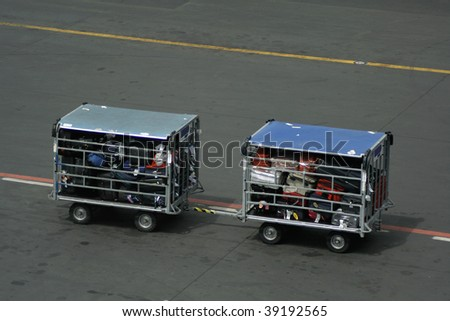 Airport vehicle transporting luggage to airplane on runway - stock photo