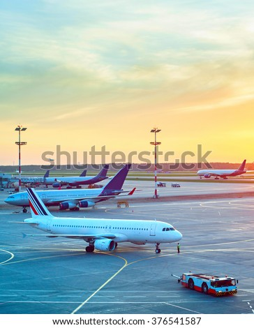 Airport with many airplanes and beautiful sunset sky - stock photo