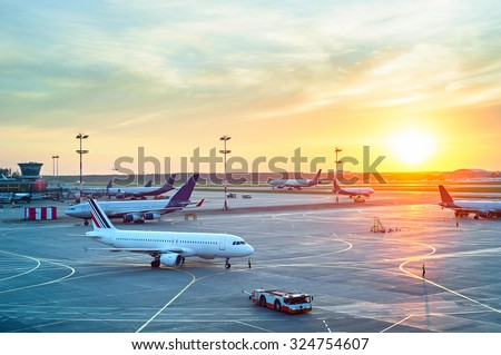 Airport with many airplanes at beautiful sunset - stock photo