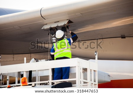 Airport worker refuelling the aircraft - stock photo