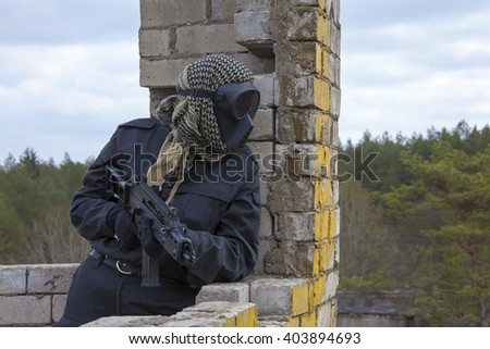 Airsoft player in black mask holding position in ruins - stock photo