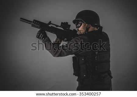 airsoft player with gun, helmet and bulletproof vest on gray background - stock photo