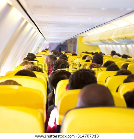 Aisle inside a plane. Interior with passengers on the seats - stock photo