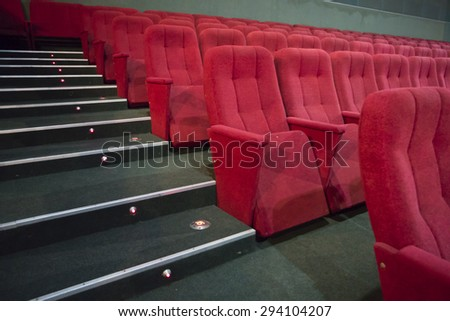 Aisle with rows of red seats in the modern theater - stock photo