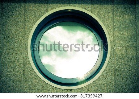 Ajar round window on the tiled granite wall - part of the urban architecture. Toned. - stock photo