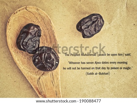 Ajwa Dates fruit on wooden spoon in retro style (Ajwa is a soft dry variety of date fruit from Saudi Arabia. It is cultivated at the city of Madinah) - stock photo
