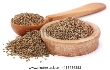 Ajwain seeds in a wooden bowl and spoon over white background - stock photo