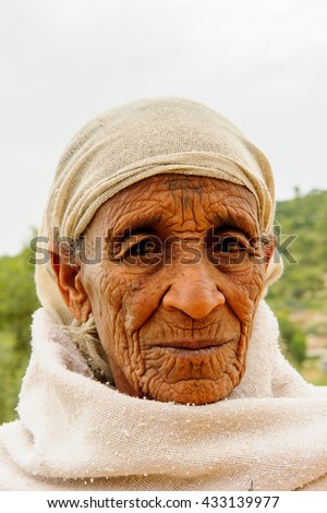 AKSUM, ETHIOPIA - SEP 24, 2011: Unidentified Ethiopian old woman in white clothes in Ethiopia, Sep.24, 2011. People in Ethiopia suffer of poverty due to the unstable situation - stock photo