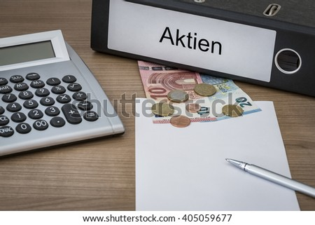 Aktien (German stock) written on a binder on a desk with euro money calculator blank sheet and pen - stock photo