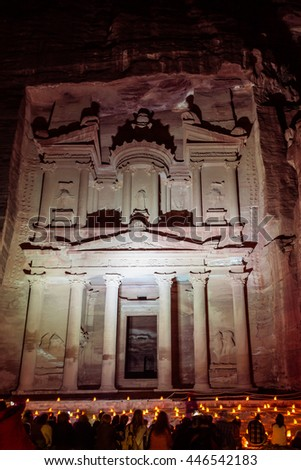 Al Khazneh in the ancient  city of Petra in Jordan at night lighted in different colors and hundreds of candles in the front. - stock photo