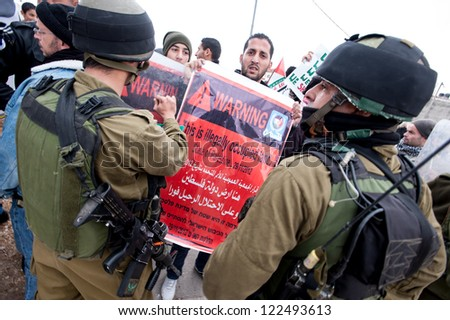 AL MASARA, PALESTINIAN TERRITORY - DECEMBER 4: Palestinians confront Israeli soldiers during a demonstration against the separation wall in the West Bank village of Al Ma'sara, December 14, 2012. - stock photo