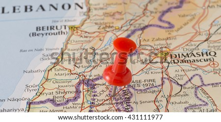 Al Qunaytirah marked on map with red pushpin. Selective focus on the word Al Qunaytirah and the pushpin. Pin is in an angle. Midground is sharp while foreground and background is blurry. - stock photo