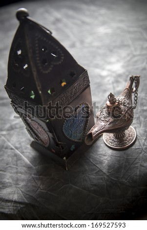 Aladdin Lamp & Egyptian fanous on grey textile - stock photo