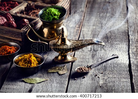 Aladdin Lamp from bronze and dry spices at wooden background with spoons nearby - stock photo