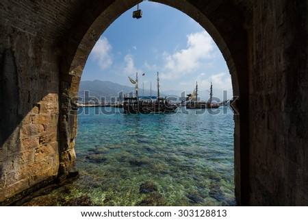 ALANYA, TURKEY - JULY 04, 2015: Traditional entertainment resort of Alanya. Sailing aka pirate ships around the fortress of Alanya. View from the medieval shipyard (Tersane) of the Alanya Castle. - stock photo