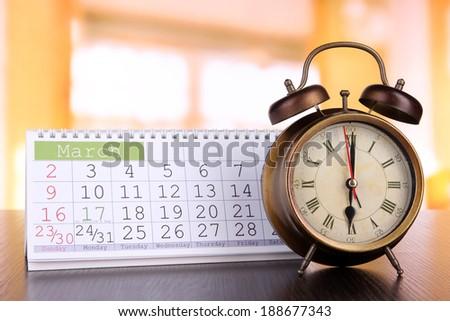 Alarm clock  and calendar on bright background - stock photo
