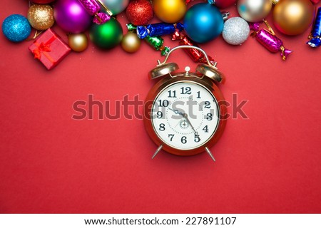 Alarm clock and christmas toys on red table. - stock photo